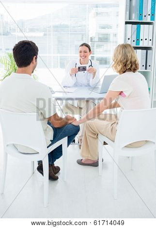 Expectant couple consulting female doctor in clinic