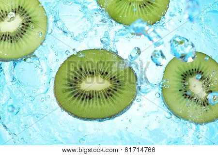 splashing water on kiwi slices - blue background
