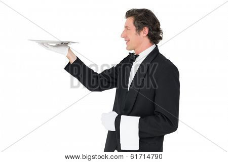 Smiling waiter carrying tray against white background