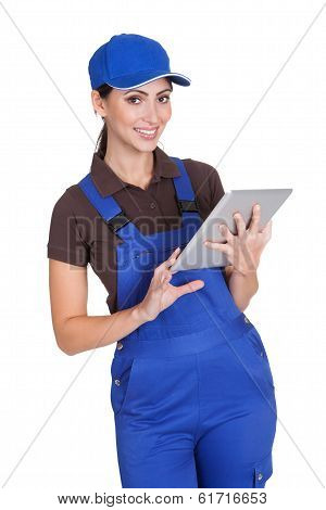 Smiling Female Plumber Working On Digital Tablet