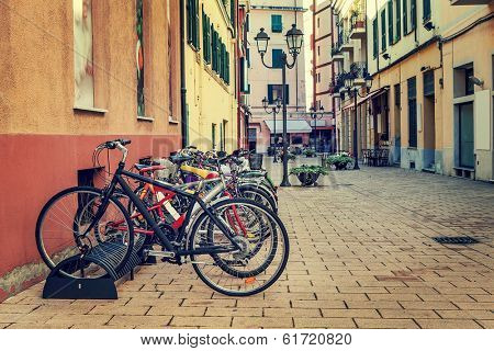 Different types of city bicycles in a row on parking on the street in ventimiglia, Italy.
