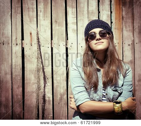 beautiful cool girl in hat and sunglasses against grunge wooden fence, toned