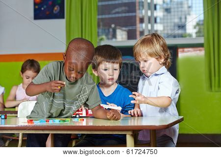 Children playing together in kindergarten group with building blocks and a firetruck