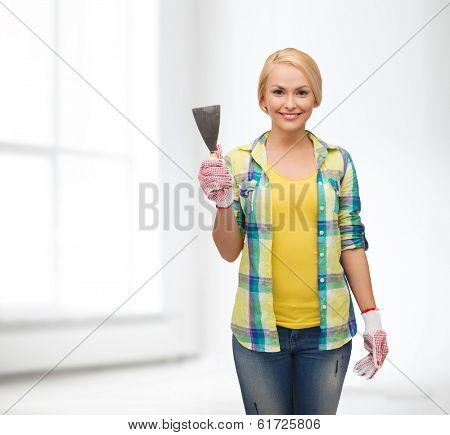 repair, construction and maintenance concept - smiling female worker in gloves with spatula