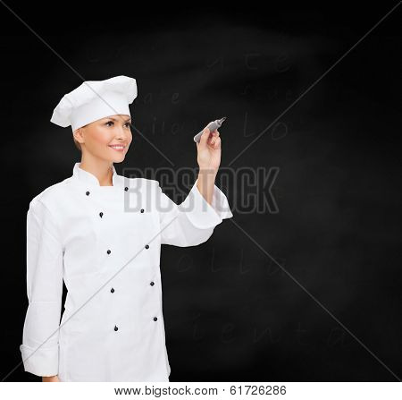 cooking, new techology , advertisement and food concept - smiling female chef, cook or baker with marker writing something on virtual screen