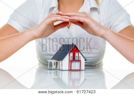 house is protected. woman holding hands over model house