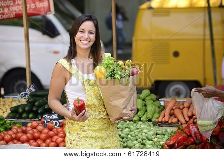 Happy women consumer at an open street market carrying a paper bag with full of organic  fruit and vegetables.