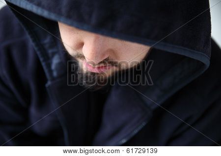 man in hooded jacket looking down