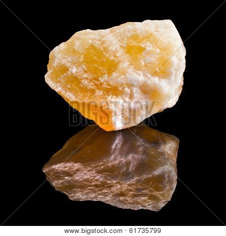 Calcite crystal with reflection on black surface background