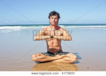 Young handsome man meditating on the beach