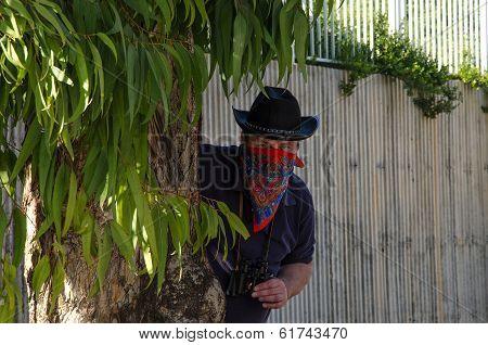 Cowboy Ambushing In Bandana Behind Eucalyptus