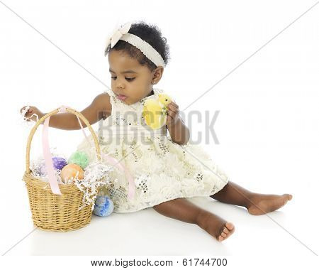 A beautiful baby girl, all dressed up, exploring her first Easter basket.  On a white background.