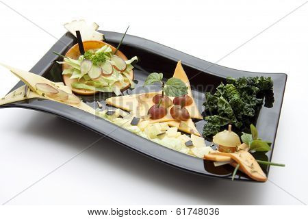 Fresh Cold Cuts from Cheese with Grapes and Salad Sheets in Black Ceramic Plate