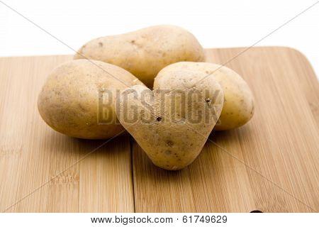 Fresh Brown Potatoes on Cutting Board