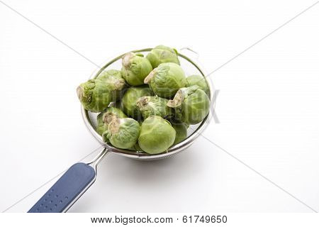 Green Brussels sprouts with culinary sieve
