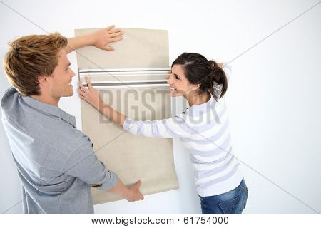 Young couple choosing wallpaper for new home