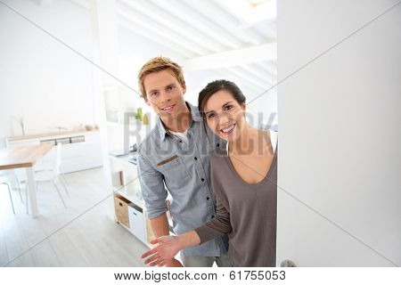 Young couple inviting people to come in new place