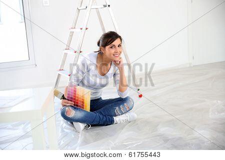 Brunette girl having a break while renovating home