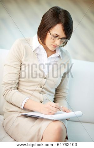 Vertical image of a professional counselor taking notes