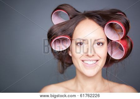Headshot of a young woman with hair curlers over grey background