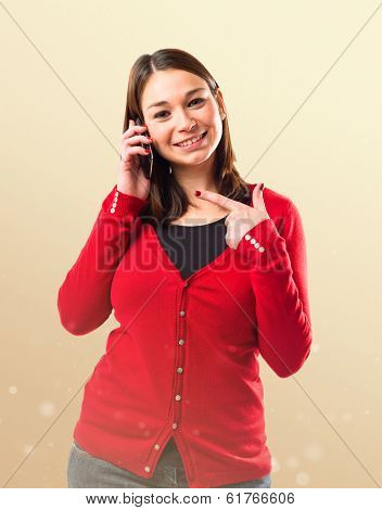 Young Girl Talking On Mobile Over Ocher Background