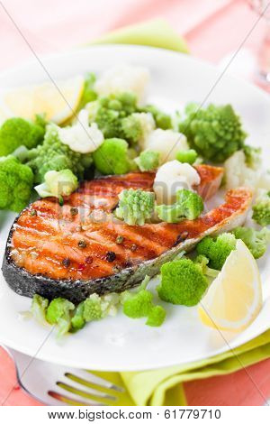 grilled salmon with broccoli and cauliflower on white plate