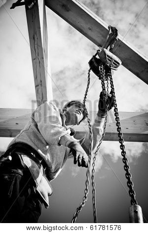 construction worker at work with winch on roof construction.Monochrome