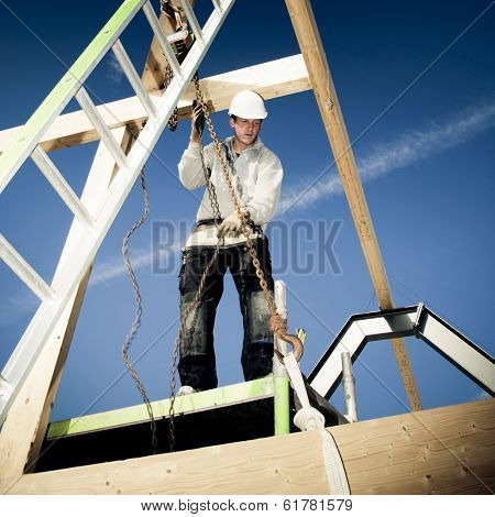 construction worker with ladder and winch on top of construction.