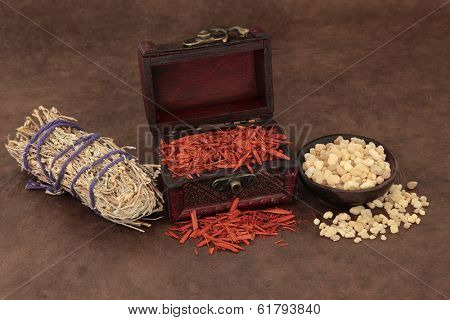 Frankincense, sandalwood and sage smudge stick incense selection over lokta paper background.
