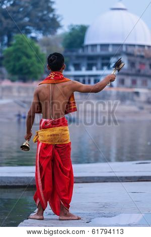 UJJAIN, INDIA - APRIL 23, 2011: Brahmin performing Aarti pooja ceremony on bank of holy river Kshipra. Aarti is Hindu religious ritual of worship part of puja when light offered to one or more deities