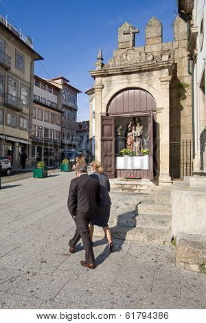 Guimaraes, Portugal - March 25, 2013: Locals pass by one of the Stations of the Cross especially open for the procession of the Easter Celebration. UNESCO World Heritage Site.