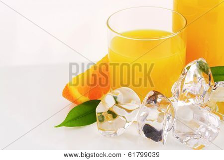 part view of bottle with juice and frozen ice cubes with fresh oranges