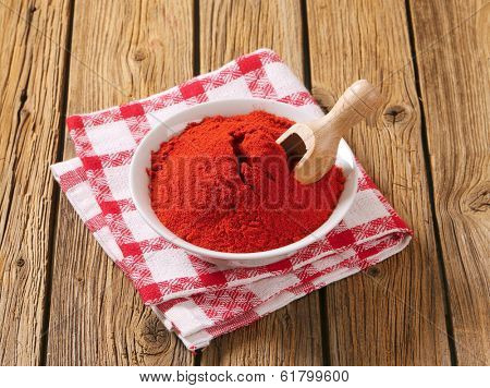 bowl with red ground pepper and immersed measuring spoon
