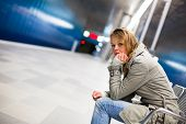 Sad and alone in a big city - Depressed young woman sitting in a metro station, feeling sorrow, regr