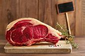 stock photo of bloody  - raw beef Rib bone  steak   on wooden board and table with empty black sign - JPG