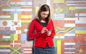 Young Girl Sending A Message With Her Mobile Over Flags Background