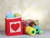 picture of lurex  - Bags with bobbins of colorful thread and woolen balls on wooden table - JPG