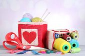 stock photo of lurex  - Bags with bobbins of colorful thread and woolen balls on wooden table - JPG