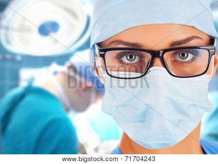 Young female surgeon in operation room with surgeons on background.
