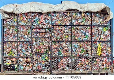 plastic bottles lie in a heap in metal cage