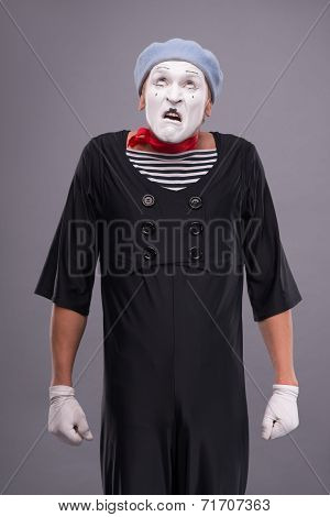 Portrait of funny male mime with grey hat and white face isolate