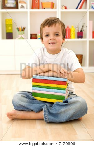 Schoolboy With Books Sitting On The Floor