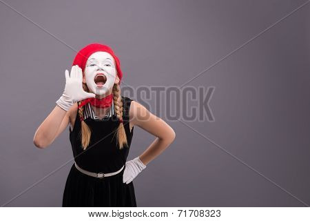 Portrait of female mime in red head and with white face isolated