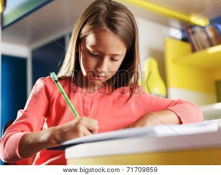child concentrating on homework in bedroom