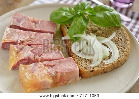 Beef tongue in aspic with basil and onion on the slice of bread