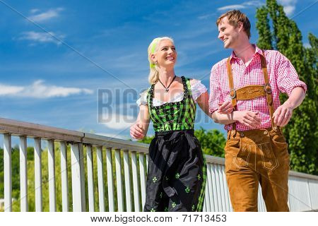 Couple visiting together Bavarian fair in national costume leather pants and Dirndl