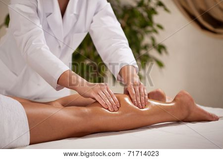 Masseur Massaging Woman's Calf