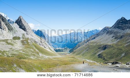 SEIGNE HILL, ITALY - AUGUST 27: Hikers on hill path with snowy Grand Combin mountain in the background. The region is a stage of the popular Mont Blanc tour. August 27, 2014 in Seigne Hill.