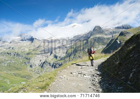 VILLE DES GLACIERS, FRANCE - AUGUST 27: Hiker walking towards Glacier Needles. The region is a stage at the Mont Blanc tour, which crosses three countries. August 27, 2014 in Ville des Glaciers.
