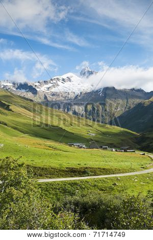 VILLE DES GLACIERS, FRANCE - AUGUST 27: Small village with Glacier Needles in the background. The region is a stage at the popular Mont Blanc tour. August 27, 2014 in Ville des Glaciers.
